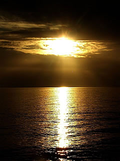 Click to enlarge this beautiful public domain copyright free photograph of the sun in the clouds over the ocean like God's Eye watching over us and beckoning us to seek him out.